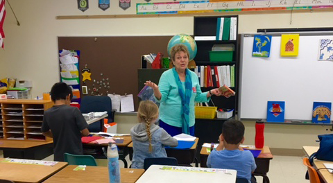 Senior citizen working with elementary school students.
